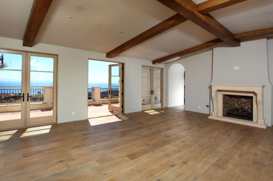 The open, airy room with exposed wooden beams, a series of French doors that lead out onto a balcony, and a stone fireplace mantle with multi-colored brick work on the inside.
