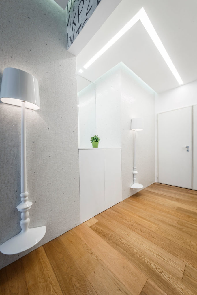 The ceiling in this space runs with a central recessed lighting track, over the crystal adorned wall and white lamps.
