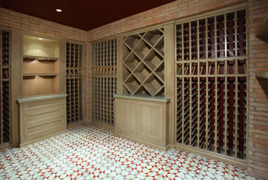 The empty wine cellar, with a bold patterned tile floor and brick walls around the built-in storage.