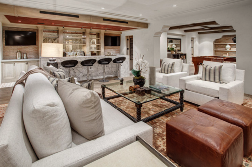 A fresh coat of paint, modern barstools, a white linen sofa with two matching armchairs, dual leather ottomans in a rich red-brown, and a large ornate glass coffee table fill the large room. On the other side of the wide archway is a continuation of the space, complete with a game table.