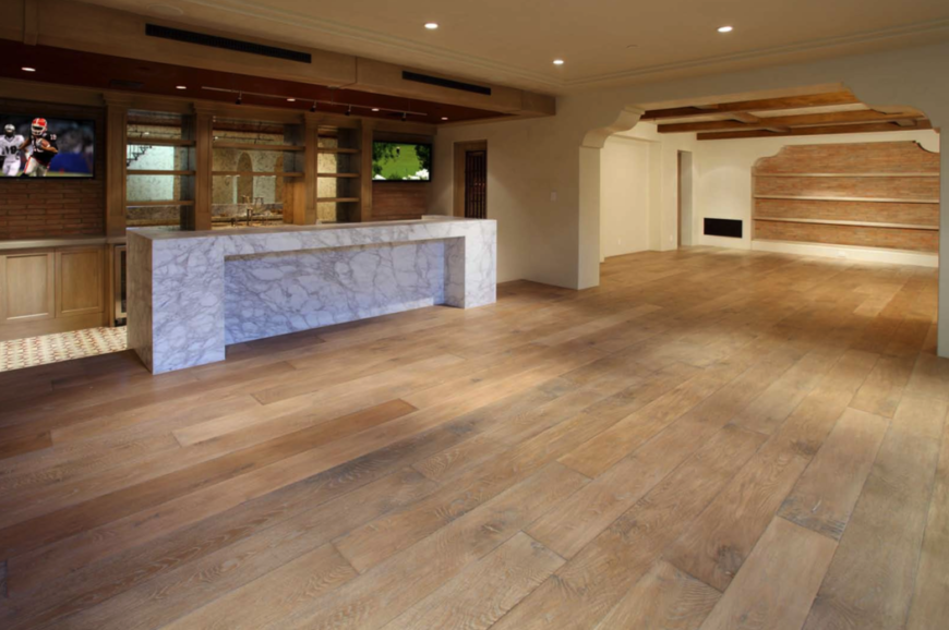 The bare, hollowed out, cavernous room with light hardwood floors, exposed beams on the ceiling, and a large, solid marble wet bar on the left. On either side of the bar are televisions, marking this space as one for casual entertainment.