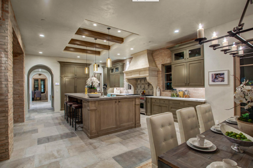 The spacious kitchen, with all the furniture, accents, and decor added, becomes a welcoming, cozy place. A beautiful dining set with upholstered chairs, set with pristine white dishes and a white orchid that matches the one on the kitchen island help make the home feel clean, but lived-in.