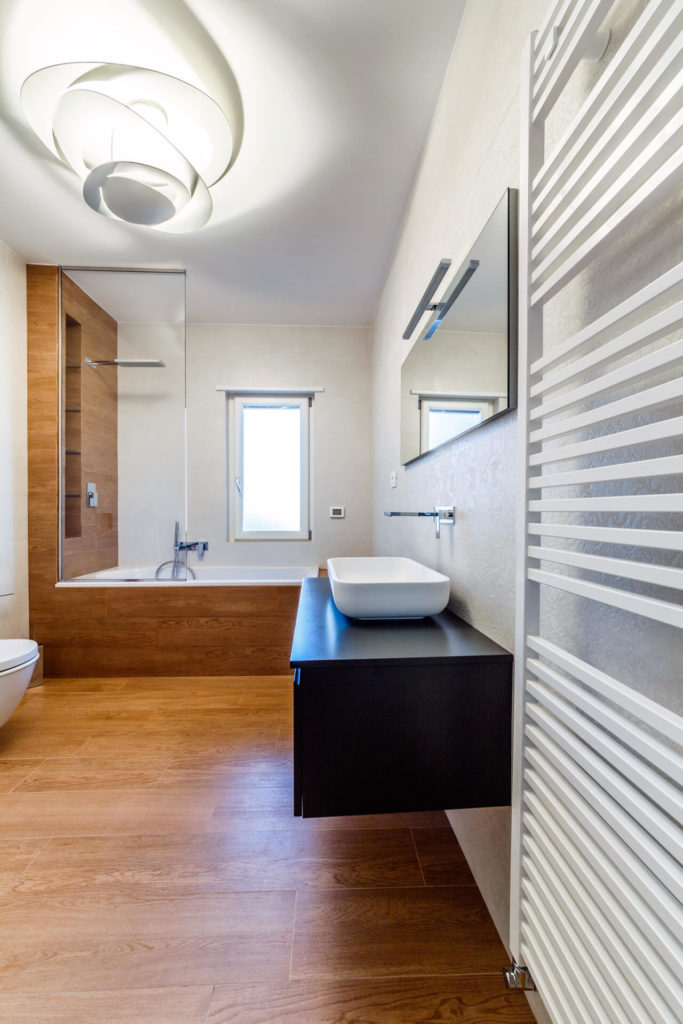 The master bath is overseen by a large ultra-modern lighting solution in white, with wood wrapped soaking tub at far end. Floating vanity in black holds a white vessel sink.
