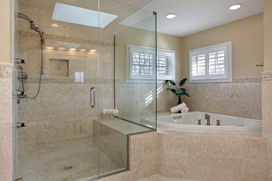 The skylight in this bathroom can be seen in reflection on the clear glass doors of the enclosed shower space. The deep creamy beige of the tiled walls is textured with the natural veins of the stone. More intricate tile-work is noted on the floor of the shower space, and is mimicked around the perimeter.