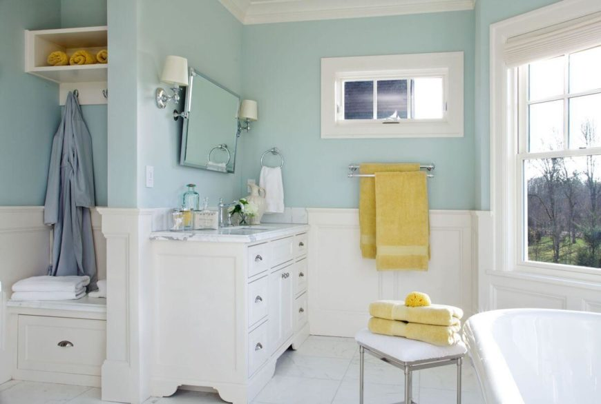 A white and robin's egg blue bathroom with sunny yellow accents. A small bench with storage hooks and a pull-out drawer acts as extra towel storage. The wall-mounted mirror can be adjusted for the perfect angle.