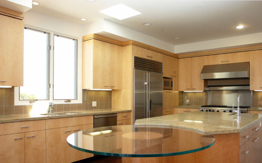 This seamless design has a glass table coming off of the island. A small skylight adds a subtle highlight to the main area of the kitchen.