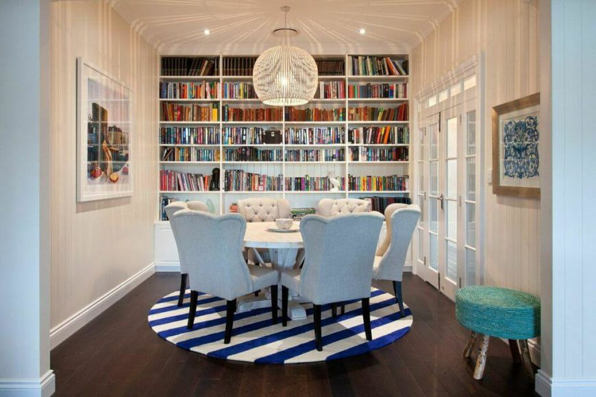 The dining room features an enormous built-in bookcase that reaches the high ceilings, with an orb chandelier above the shabby-chic wooden dining table. French doors on the right lead into the main hallway of the second story.