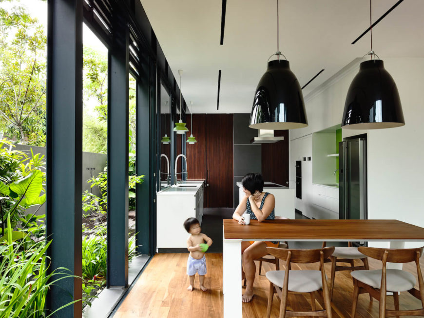 Behind the living room is a small dining room with a white and natural light wood table directly adjacent to the minimalist kitchen.