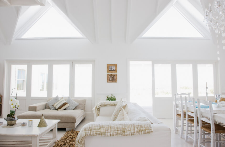Two grand skylights stand out in this high-ceiling living room. The all white color scheme with accents of taupe flourishes under the natural lighting from the windows and skylights.