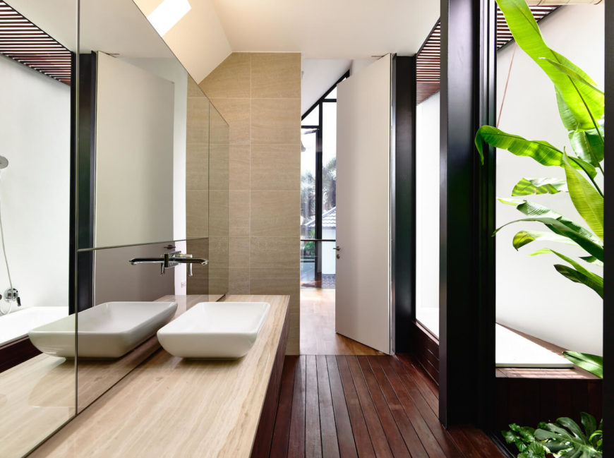 One of the upstairs bathrooms in natural wood and sandy tile with an enclosed soaking tub between black pillars. Leafy greenery makes its way into this minimalist bathroom via the houseplants and ground cover near the bathtub.