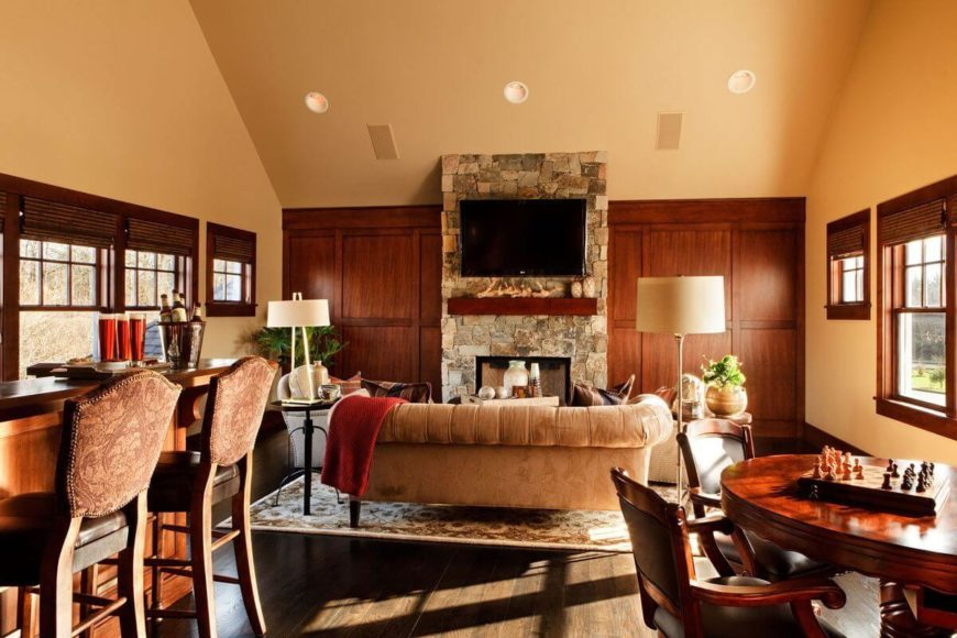 The home's less formal living room has the feel of a lounge, with a home bar, cozy seating area, and a rich wood gaming table.
