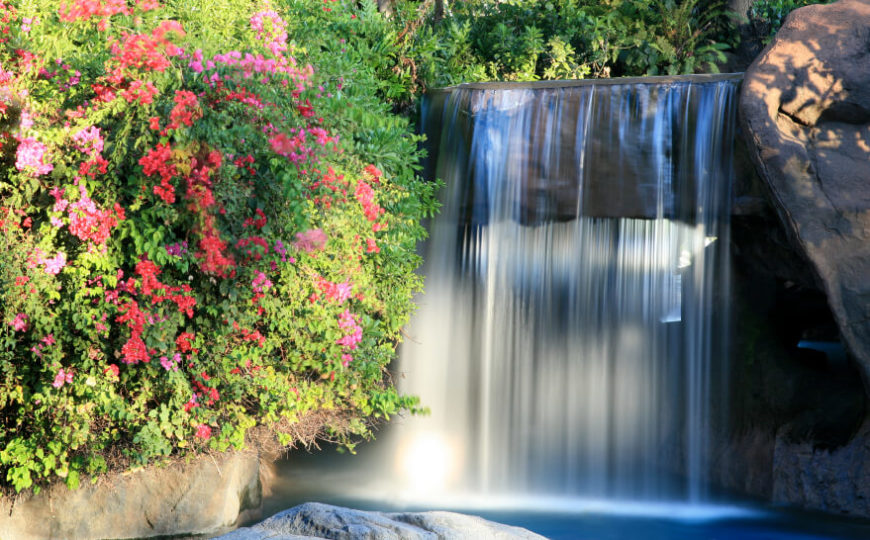 """A constantly cascading waterfall falling in a steady sheet on either side of an artificial stone """"bridge."""" Flowering bushes grow in a thick mass above the pool."""