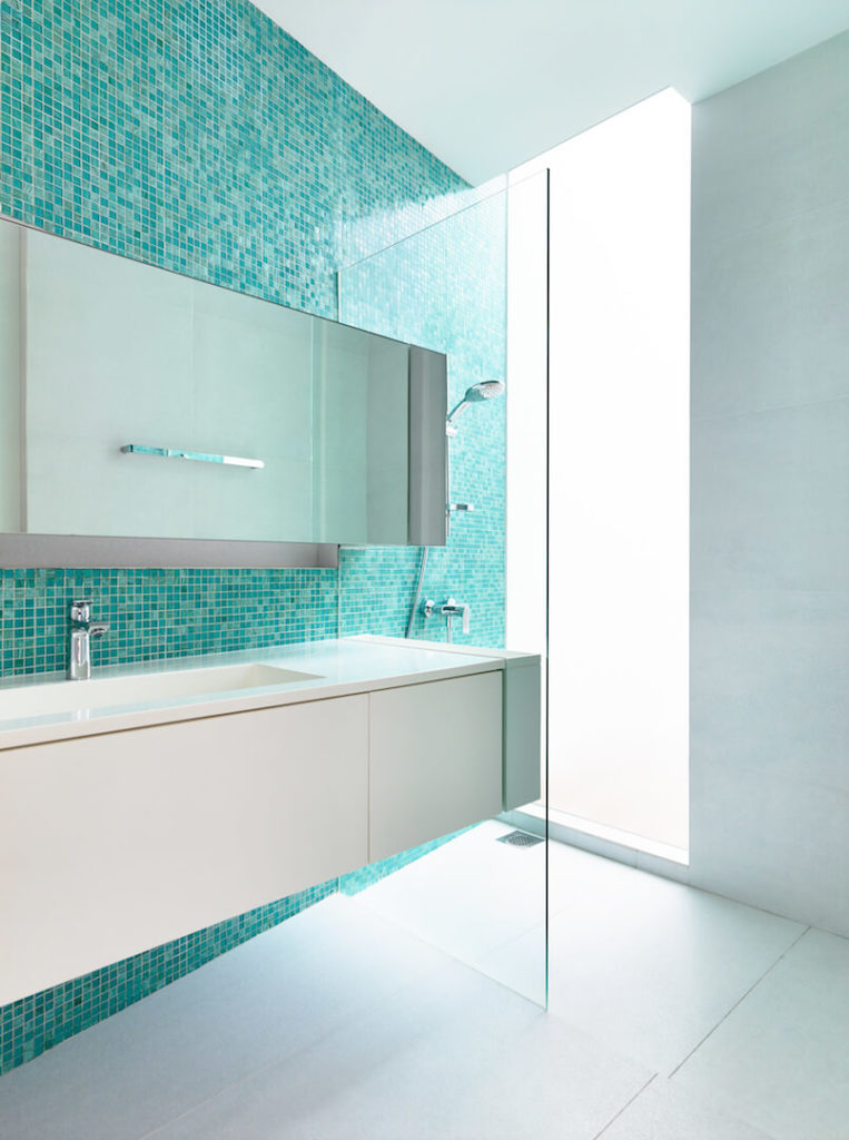 A more modern bathroom with none of the natural features in the previous bathroom. The floor-to-ceiling blue glass tile behind the floating vanity are a stark contrast to the pristine while floors, vanity, and the three other walls. A floor-to-ceiling window in the shower stall allows the terrace to be enjoyed from behind the privacy screen.
