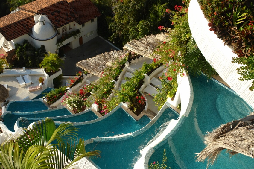 Aerial view of a resort with swimming pools cascading down along with the water.