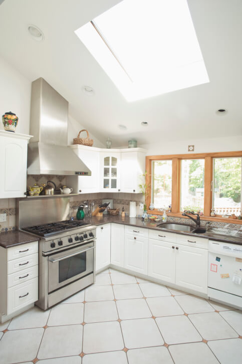 This beautiful white kitchen is quaint and cute. A large skylight accentuates the hints of salmon hues in the floor.