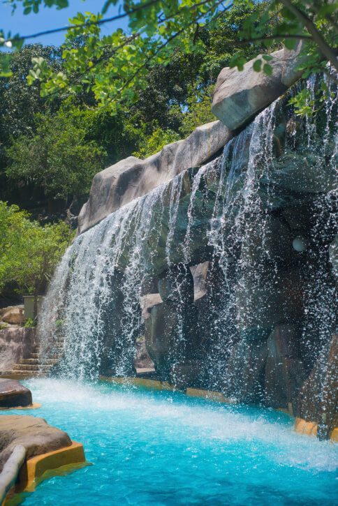 """A large, wide waterfall dumping into a """"lazy river"""" portion of a pool complex. A set of stairs leads up from the edge of the pool just beyond the waterfall."""