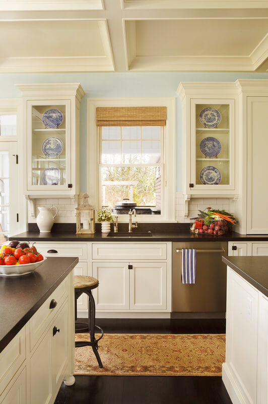 The other side of the kitchen has yet another countertop with glass-faced display cabinets on either side of the sink. Natural fiber roman shades cover the window above the sink.