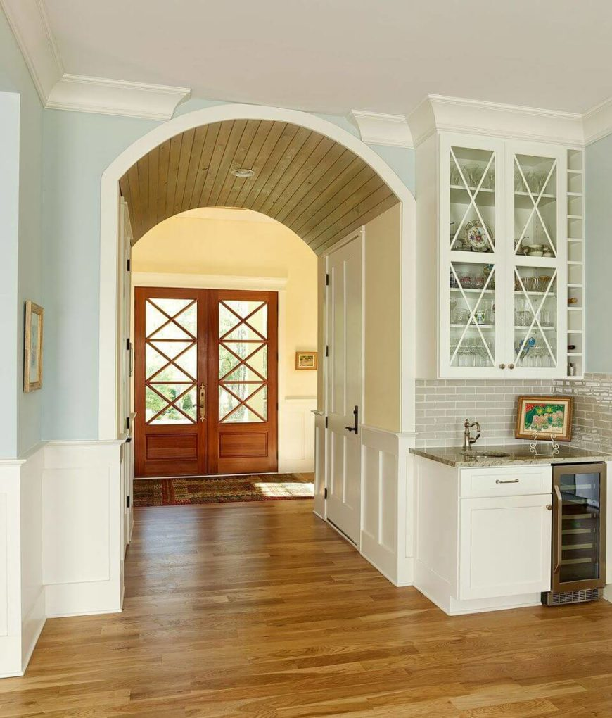 "The grand double doors with ""X"" details on the windows lead into the small foyer with a closet, stairs to the next floor, and easy access to the sizable kitchen. From this angle we can see the light taupe ceramic subway tiling above a small cabinet with a wine cooler and a small sink."