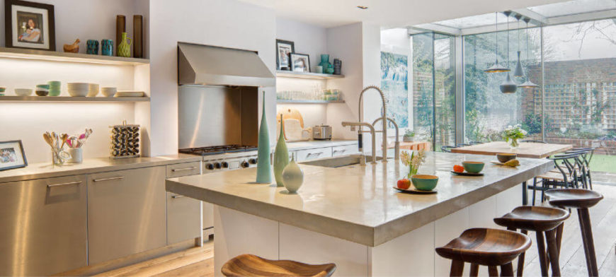 The addition comes directly off of the kitchen, which has been remodeled into a contemporary, sleek, bright kitchen with carved wooden barstools at the eat-in kitchen island. The open shelving to the left of the vent hood and range is backlit.