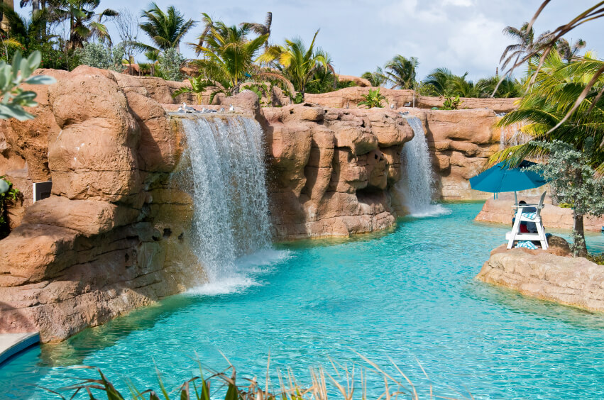 A massive, crystal blue pool with multiple artificial waterfalls tumbling down from the high artificial stone cliffs. In the center of the pool is a lifeguard stand.