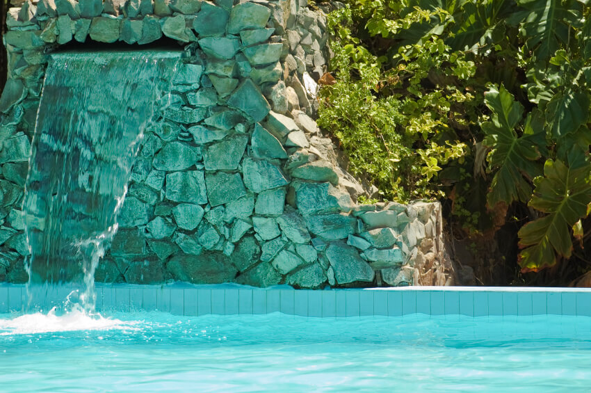 A water feature waterfall constructed of mortar and stones of varying sizes and shapes. A steady cascade of water pours out of the mouth of the waterfall and into the pool below.