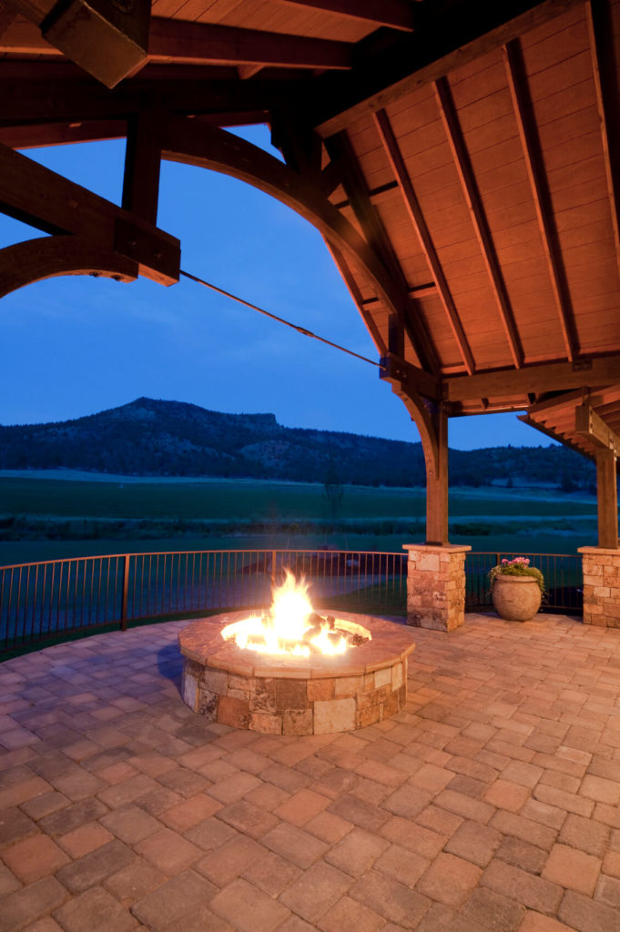 Another soaring arched roof above a stone patio, but this beautiful example features a stone fire pit that's perfect for bonfire gatherings in the summer. The view off of this elevated patio is simply amazing.