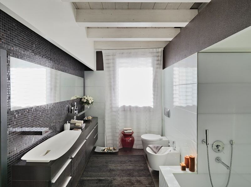 Contemporary master bathroom featuring a stylish large vessel sink set on the black counter matching the rug covering the hardwood flooring.