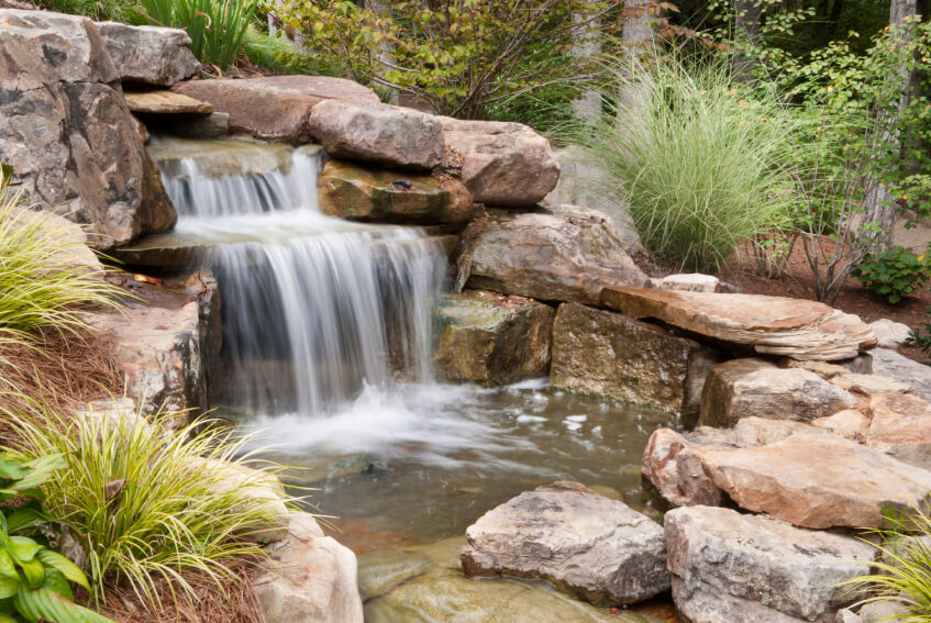 The easiest way to make a garden waterfall look and feel natural is to surround the entire enclosure, pumps and all, in natural stone boulders.