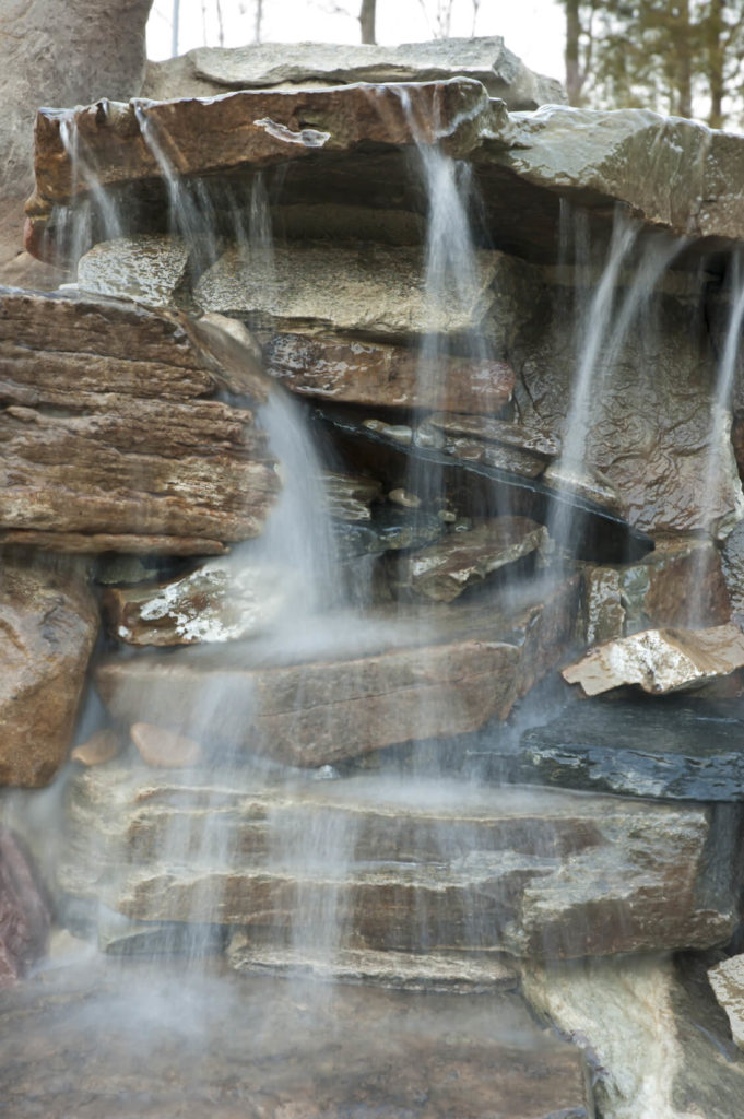A close up of a waterfall where the water hits multiple rock surfaces on the way to the bottom. Frozen in time, we can see mist and the way the water fans out.