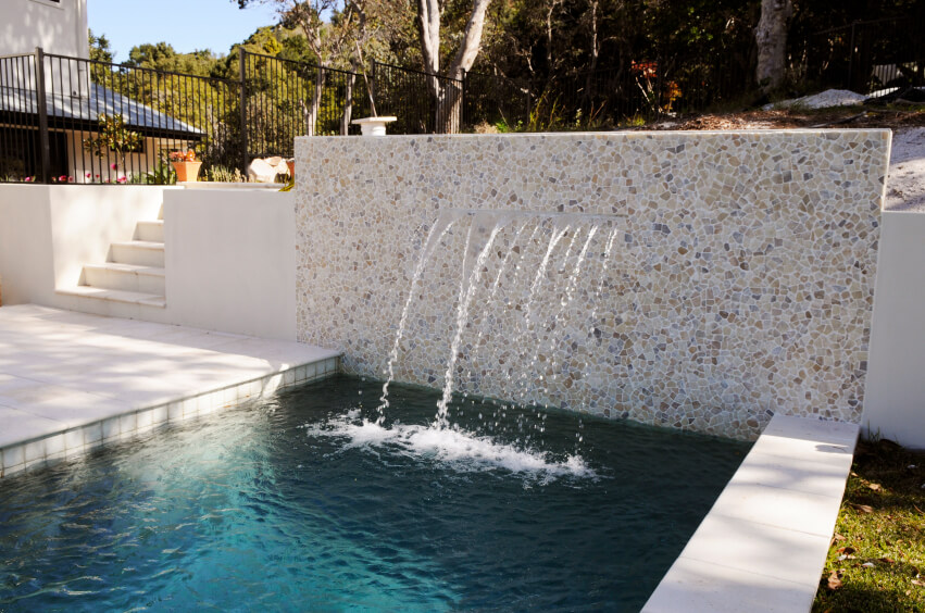 A stone and mortar wall at the edge of one pool with several fountains streaming from the horizontal crack and into the narrow, long pool.