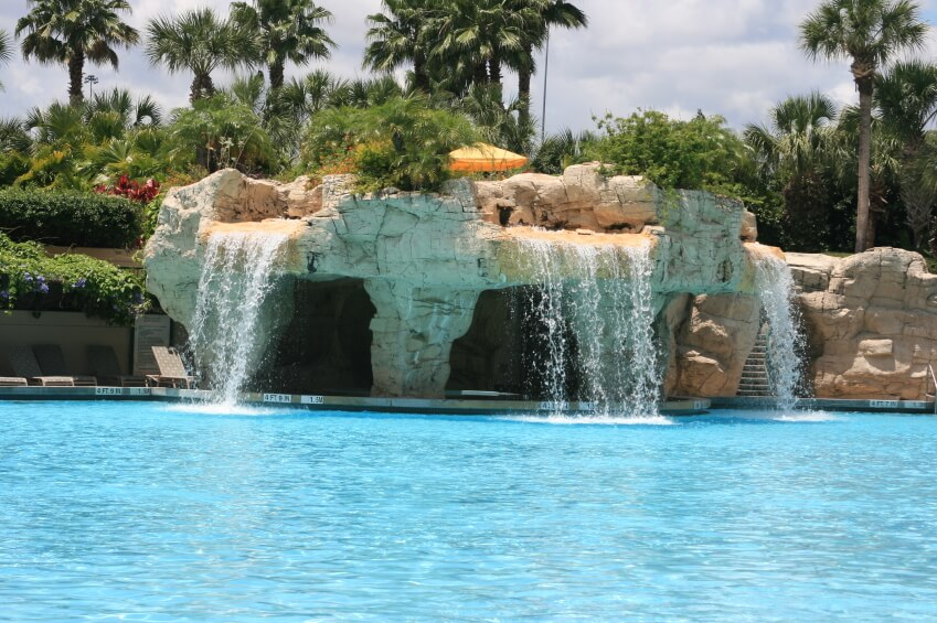 """A tropical resort pool with three waterfalls cascading down over three shadowed """"caverns"""" in the artificial stone."""