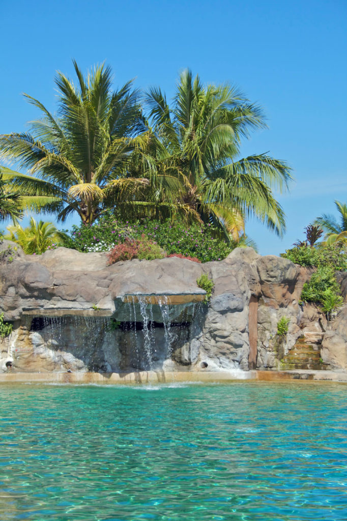 A large artificial stone outcropping follows the edge of this spacious pool, with several ledges trickling water down into the pool.