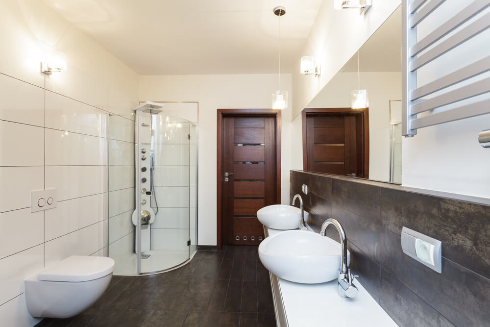 A master bathroom featuring beige walls and hardwood floors. It also boasts a walk-in shower room and a couple of vessel sinks.