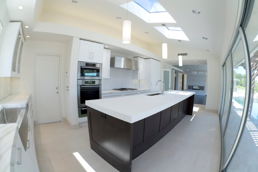 Rich Dark Hardwood Contrasts The Polished Whites And Marble Of This Kitchen.  The Skylights Dapple