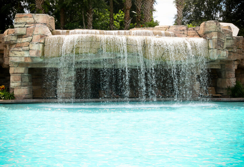 A large, stately natural stone made-made waterfall that is engineered to create a strong impression on any guests. The waterfall consists of two tiers and is overlooked by a patio.