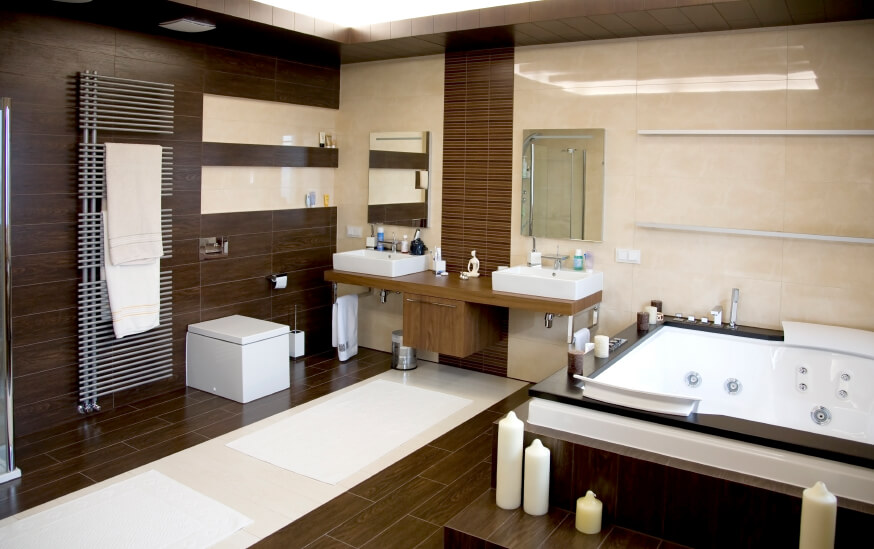 Spacious master bathroom with a pair of vessel sinks and a large drop-in tub, along with hardwood flooring and walls.