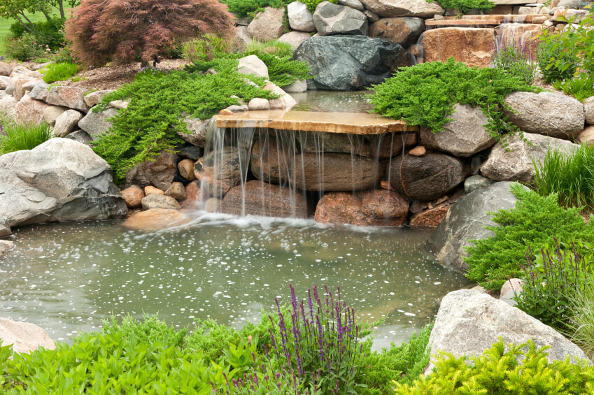 A single shelf of rock extending over the stonewall of the pond creates a simple, wide waterfall.