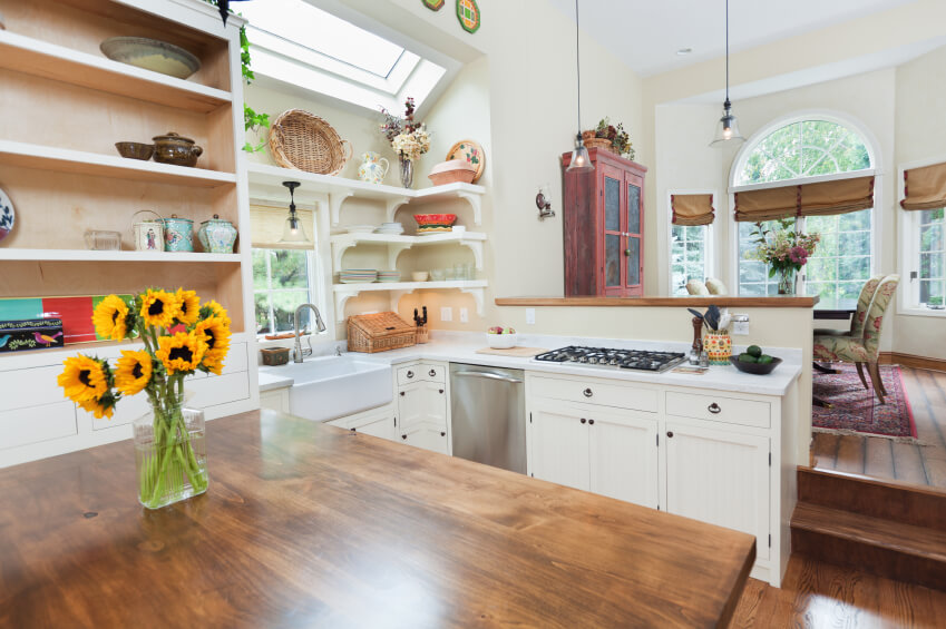 This fun kitchen is full of country decor and designs. A skylight is angled from the ceiling to pull light across the kitchen, rather than down.