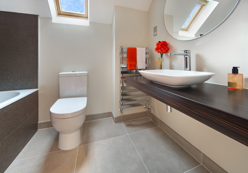 The lovely wood countertop has exquisite graining, while a modern basin sits elegantly on top. A stainless steel towel rack holds decorative hand towels, offering a bright splash of color coordinating with a small floral arrangement. A skylight hovers above the toilet and bathing area.