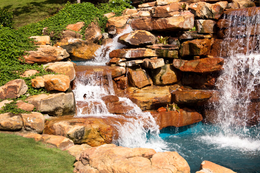 An enormous mad-made stone waterfall with succulents and ground cover growing between the cracks. The water flows down two sides of the stones, gently on the left and more thunderously on the right.