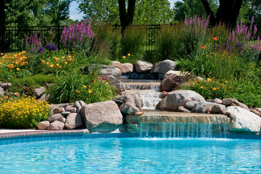 A beautifully created stone waterfall with a reservoir surrounded by daylilies and other beautiful flowering bushes.