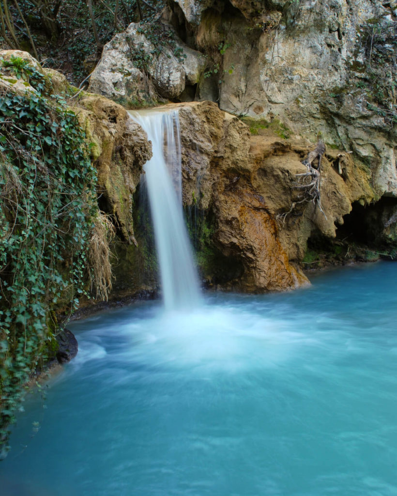 A natural pool with a beautiful waterfall tumbling down the stone walls with algae and moss growing on the damp walls.