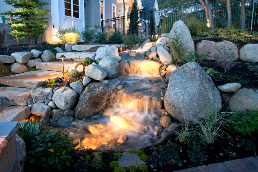 The entrance to this gated backyard runs past a small waterfall and continues into a small river that winds throughout the backyard.