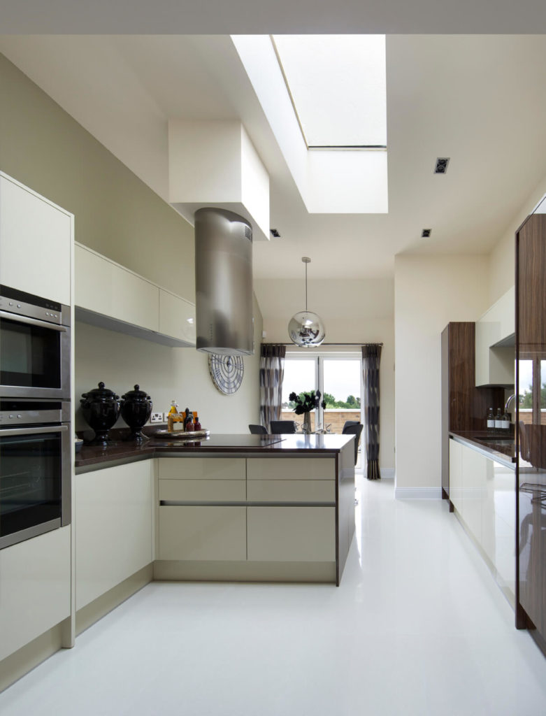 This chic kitchen is glimmering and polished. A large rectangular skylight illuminates the fresh atmosphere of this space.