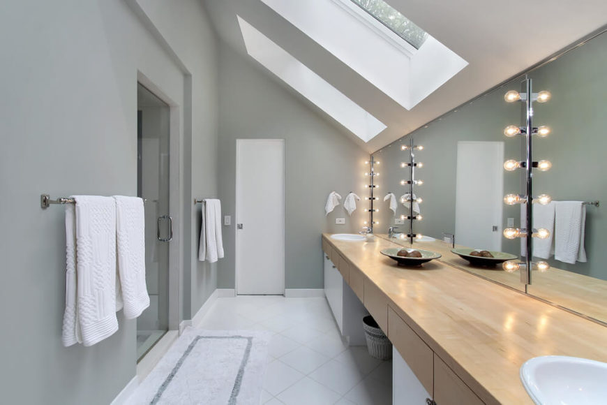 The matte gray walls of this modern bathroom contrast beautifully with the bright white of the tile flooring. Skylights shine down, with lighted mirrors offering additional ambiance. The natural hardwood counter of the double vanity offers plenty of space.