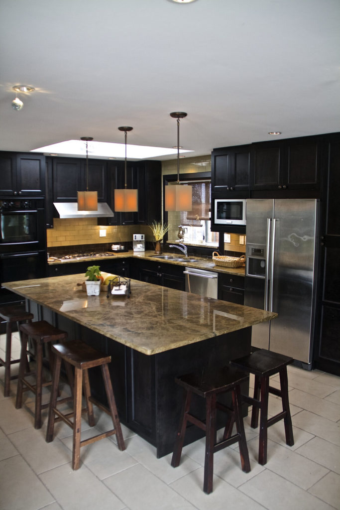 In a feat of high contrast, this skylit kitchen features black painted cabinetry, dark marble countertops, and white large format tile flooring.