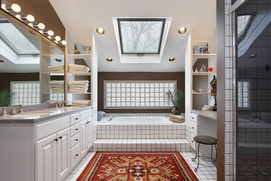 This bathroom is rich in patterns,contrast, and textures that create a dynamic and interesting space. Simple square tiles with dark grouting are mimicked in the frosted glass panel above the bathtub area. A skylight shines down, aided by recessed lighting and a simple lighting fixture above the mirror. A double vanity and shelving offer plenty of storage, while a bright rust area rug leads the way to the tiled steps of the encased bathtub.