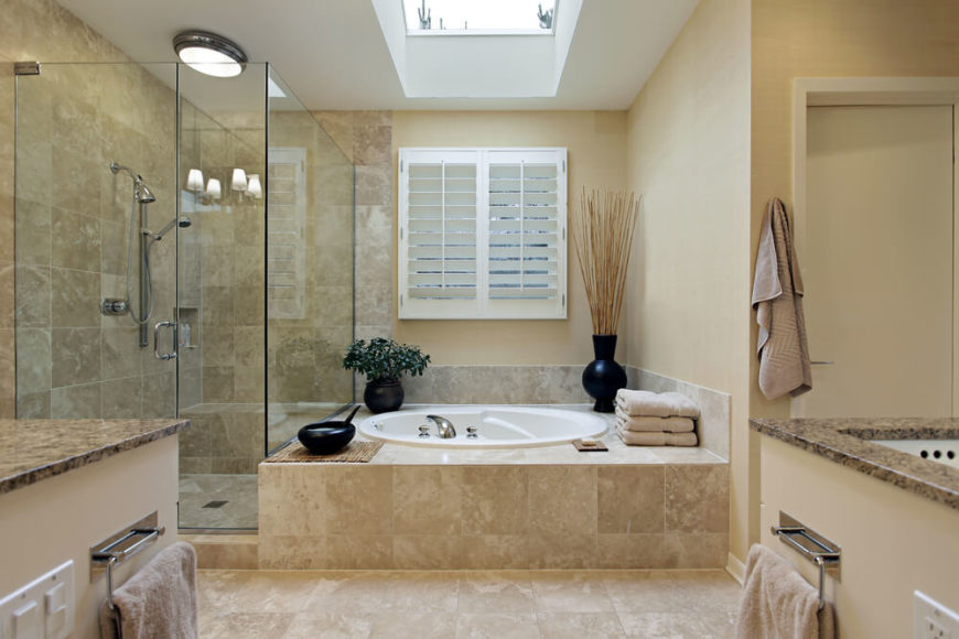 Simple country shutters filter in natural light, while a skylight allows sunshine to flood in. Additional lighting fixtures can be seen in the reflection of the glass enclosed shower, while cream vanities topped with dark marble offer a bit of contrast.