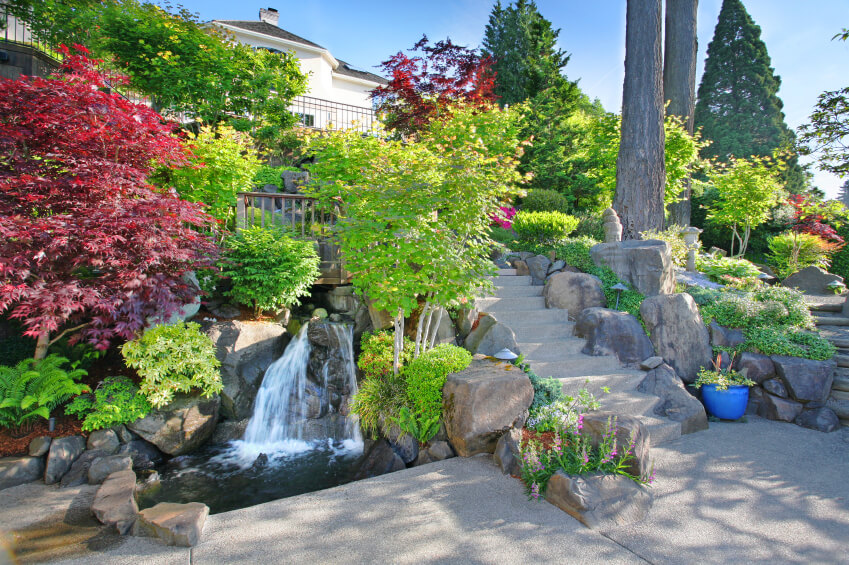 A winding stream follows the long stone stairway down to this patio. The stream ends in a small corner pool in a rush of water.