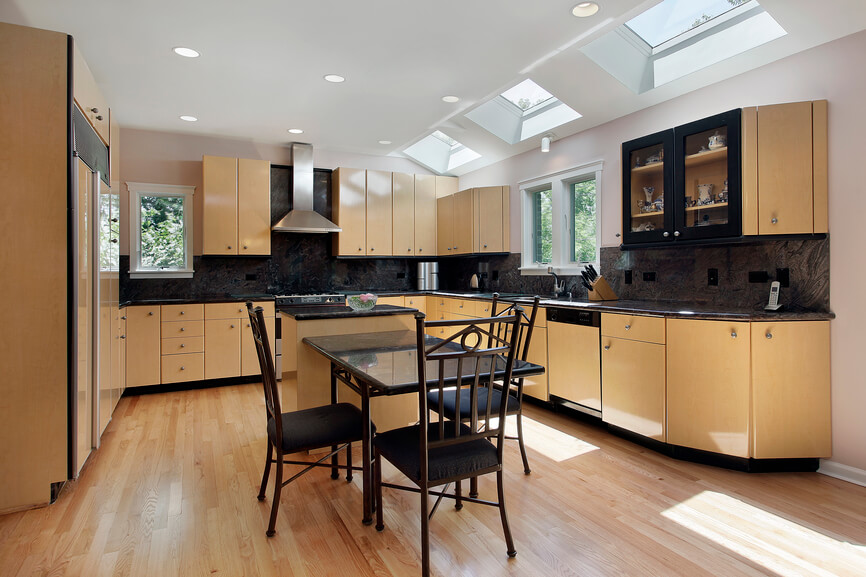 This kitchen has seamless and rounded light wood cabinets that contrast with the rich dark colors of the backsplash and table. Small skylights illuminate the center of the room.